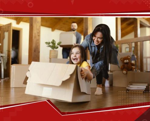 Mulher empurrando uma criança dentro de uma caixa, a criança está sorrindo.