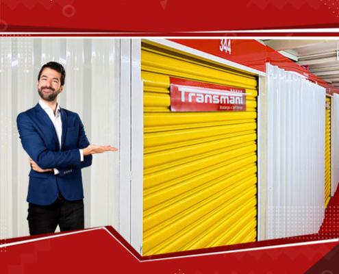 Homem apontando para boxes de self storage da Transmani